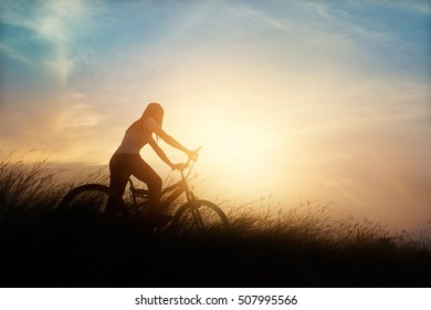 Woman with bicycle on a rural road with grass at sunset background