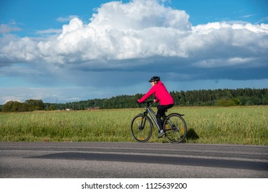 Woman bicycling on road