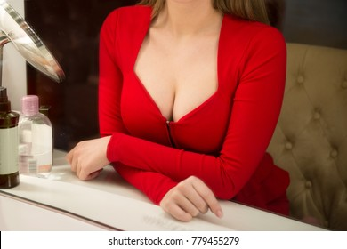 Woman with big beautiful breast wearing sexy red dress. Close-up photo of female breast.