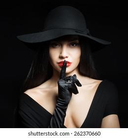 Woman in big black hat making a silence gesture, studio portrait, dark background