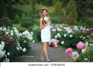Сharming woman with big bouquet peonies in basket, enjoying her flowers.Floral shop concept.Beautiful peony flower for catalog or online store. Summer holidays.Florist in garden.spring without allergy