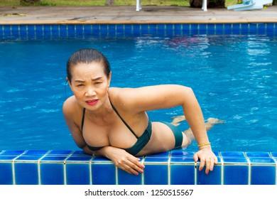 Woman big breast beautiful with bikini relax swimming pool at Bang Boet beach, Chumphion Province Thailand