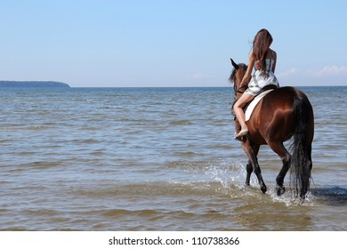Woman with big brown horse bathing in sea