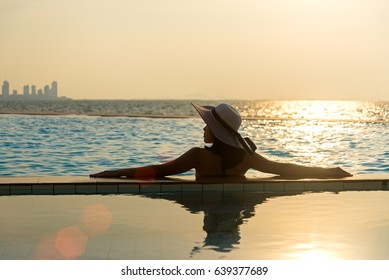 Woman in big hat relaxing on the swimming pool, near the sea in the sunset