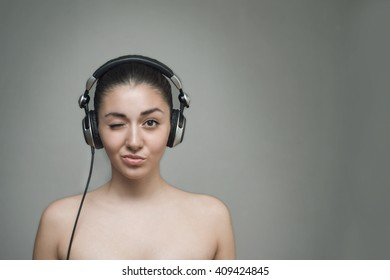 Woman with big headphones and listening to music on a grey background