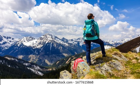 A woman with big hiking backpack hiking to Himmeleck peak, Austria. There is a massive mountain range in the back, partially covered with snow. Early spring vibes. Freedom and adventure.