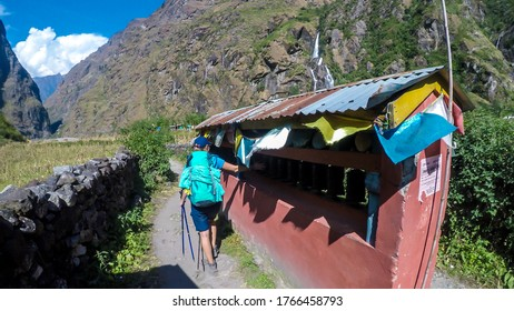 A woman with big hiking backpack spinning the prayer wheels in a small Himalayan Village, Tal, along the Annapurna Circuit Trek. In the back there are high mountain chains overgrown with greenery.