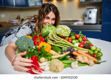 Woman with a big pile of vegetables in the kitchen