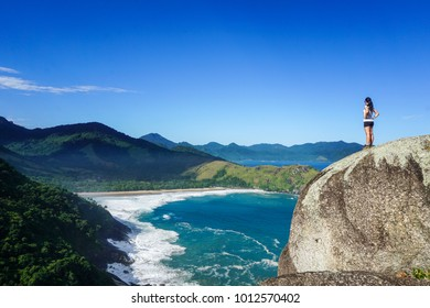 Woman in a big rock looking at Praia do Bonete (Bonete Beach) in Ilhabela (Beautiful Island), São Paulo, Brazil