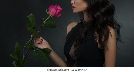Woman with big rose flower in studio at dark background
