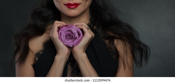 Woman with big rose in studio at dark background