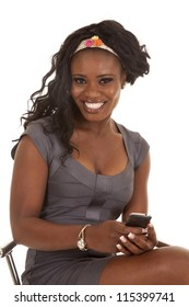 A woman with a big smile on her lips sitting on a stool with her phone in her hand.
