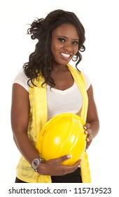 A woman with a big smile on her face holding on to her yellow hard hat.