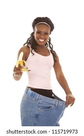 A woman with  a big smile on her face holding on to her banana and hanging on to her big pants.