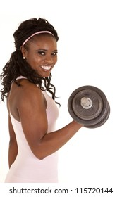 a woman with a big smile on her face lifting a weight.
