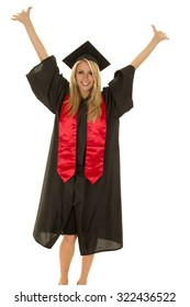 A woman with a big smile on her face with her arms raised high graduating.