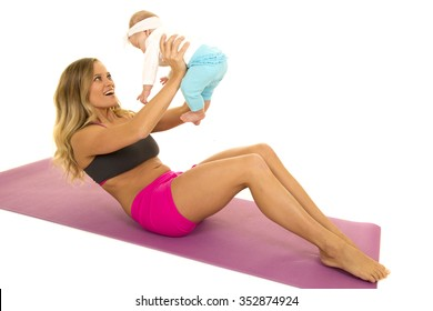 A woman with a big smile working out with her baby, being her weight.