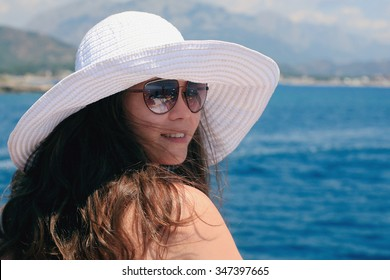 .Woman in a big white hat standing near the railing and looks at sea. Young elegant woman in hat near the sea on a summer day.