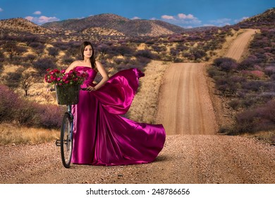 Woman with bike in a beautiful pink dress