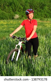 Woman and bike in a green field under summer sun