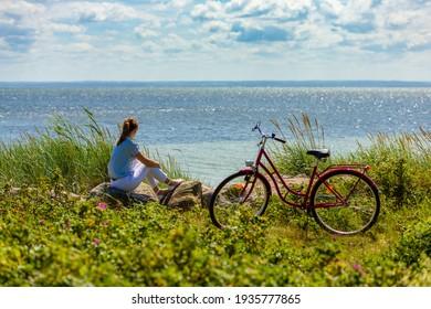 Frau mit Fahrrad am Meer