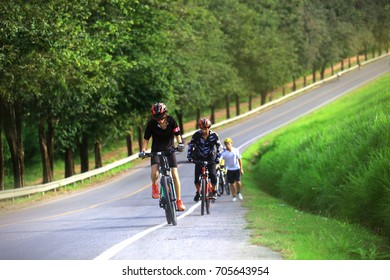 woman biker  cycling on the road with fiiends in back ground, select focus