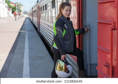 Woman biker getting intercity train with white helmet in hands and dressed in motorcycle jacket, copy space