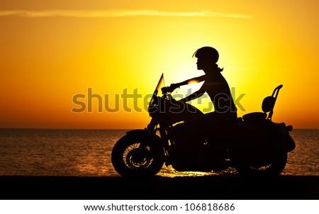 Woman biker over sunset