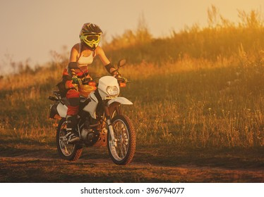 Woman biker rides in fields. Sporty woman biker at motobike. Countryside, country road.  sunset, female motorcycle rider, motorbike rider travel the world, girl resting, freedom lifestyle, back view