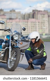 Woman biker trying to repair flat on motorcycle at city road