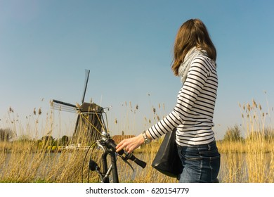 Woman bikes along windmill