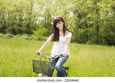 woman biking in park, smiling and looking at camera