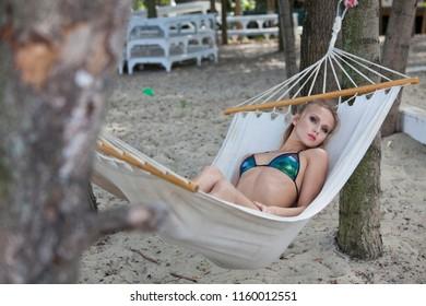 Woman in bikini chilling on Hammock