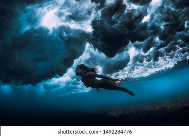 Woman in bikini dive without surfboard underwater with ocean wave. Duck dive under barrel wave