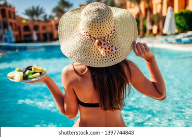 Woman in bikini eating fruits and relaxing in swimming pool. All inclusive concept. Summer vacation