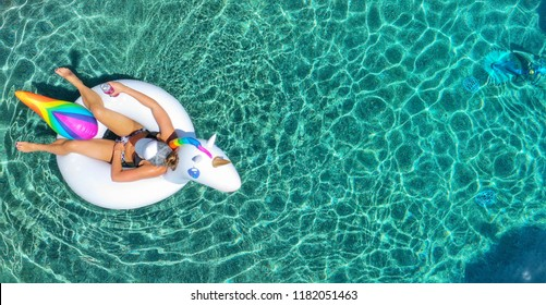 Woman in a bikini floating on a unicorn floatie