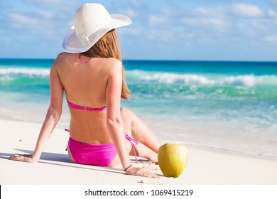 woman in bikini with fresh coconut juice on tropical beach