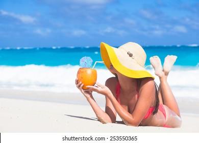 woman in bikini with fresh coconut juice on tropical beach