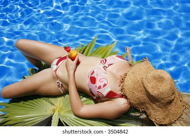 Woman in bikini and hat by bright pool with beverage