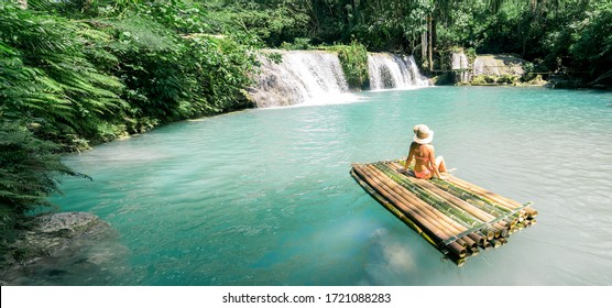 Woman in bikini and hat sitting on bamboo raft and enjoying view on waterfall. Travel and vacation concept. Banner and panoramic edition.