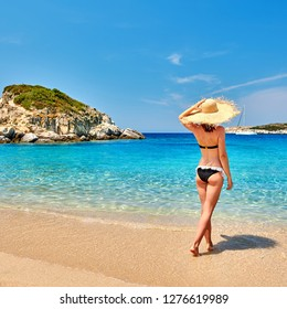 Woman in bikini on beach, Sithonia, Greece