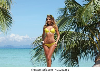 Woman in bikini on a tropical beach with palm trees