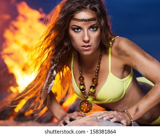 Woman in bikini is posing near a bonfire that is at the beach