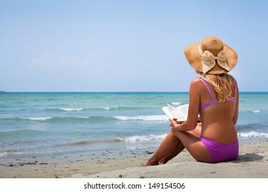 woman in bikini reading book on the beach