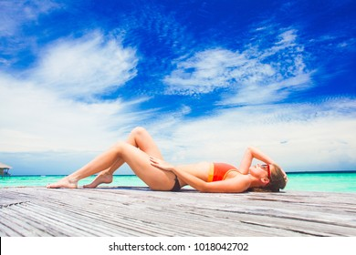 woman in bikini relaxing by the beach