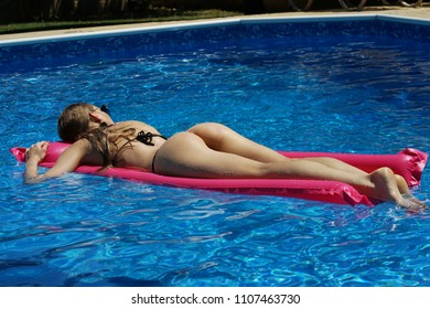 Woman in bikini relaxing on air mattress - rear view