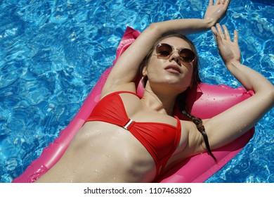 Woman in bikini relaxing on air mattress - vacation time