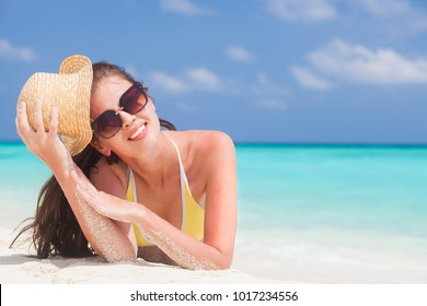 woman in bikini and straw hat lying on tropical beach