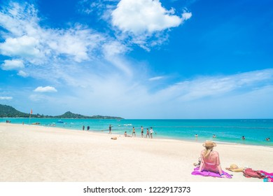 Woman in bikini with straw hat lying on tropical beach turquoise color sea many people also the beach and blue sky white sandy beach.koh