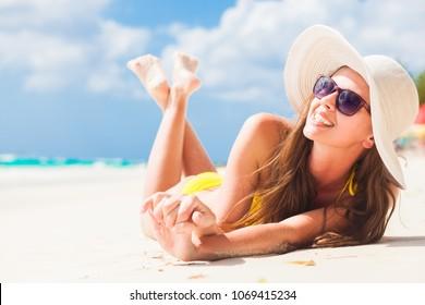 woman in bikini and straw hat relaxing on tropical beach